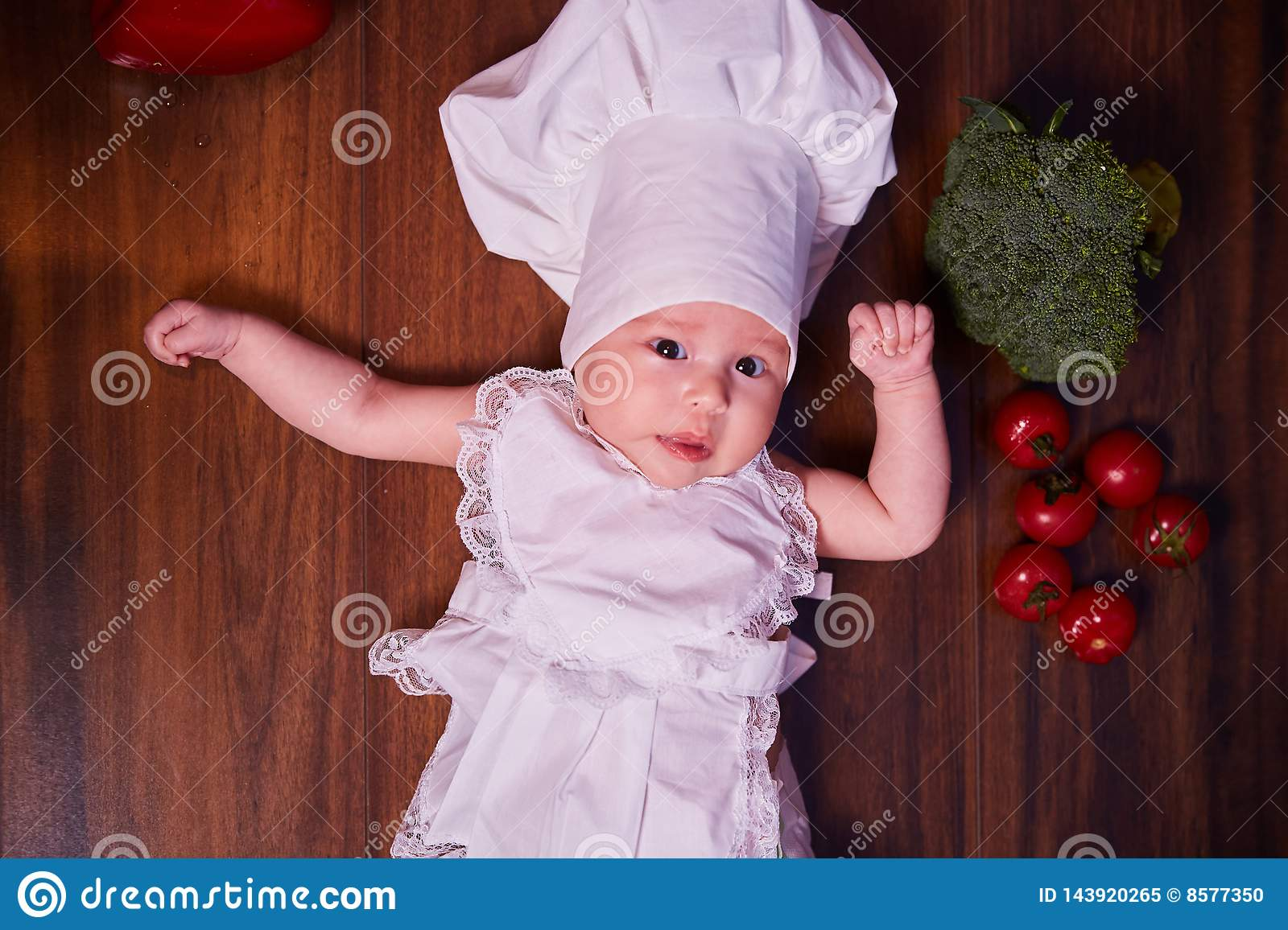 A child, baby, girl, lies on the kitchen table, in a cook`s cap and in an apron, next to him are vegetables, broccoli, tomatoes,