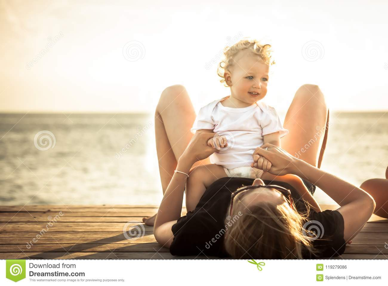 Child baby mother relaxing together beach during summer beach holidays sunlight
