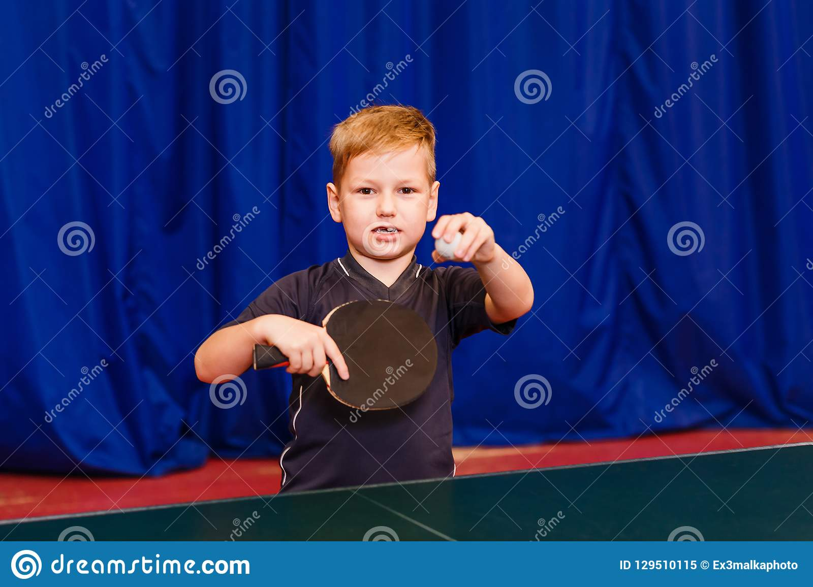 A child with a ball and a table tennis racket looks into the camera