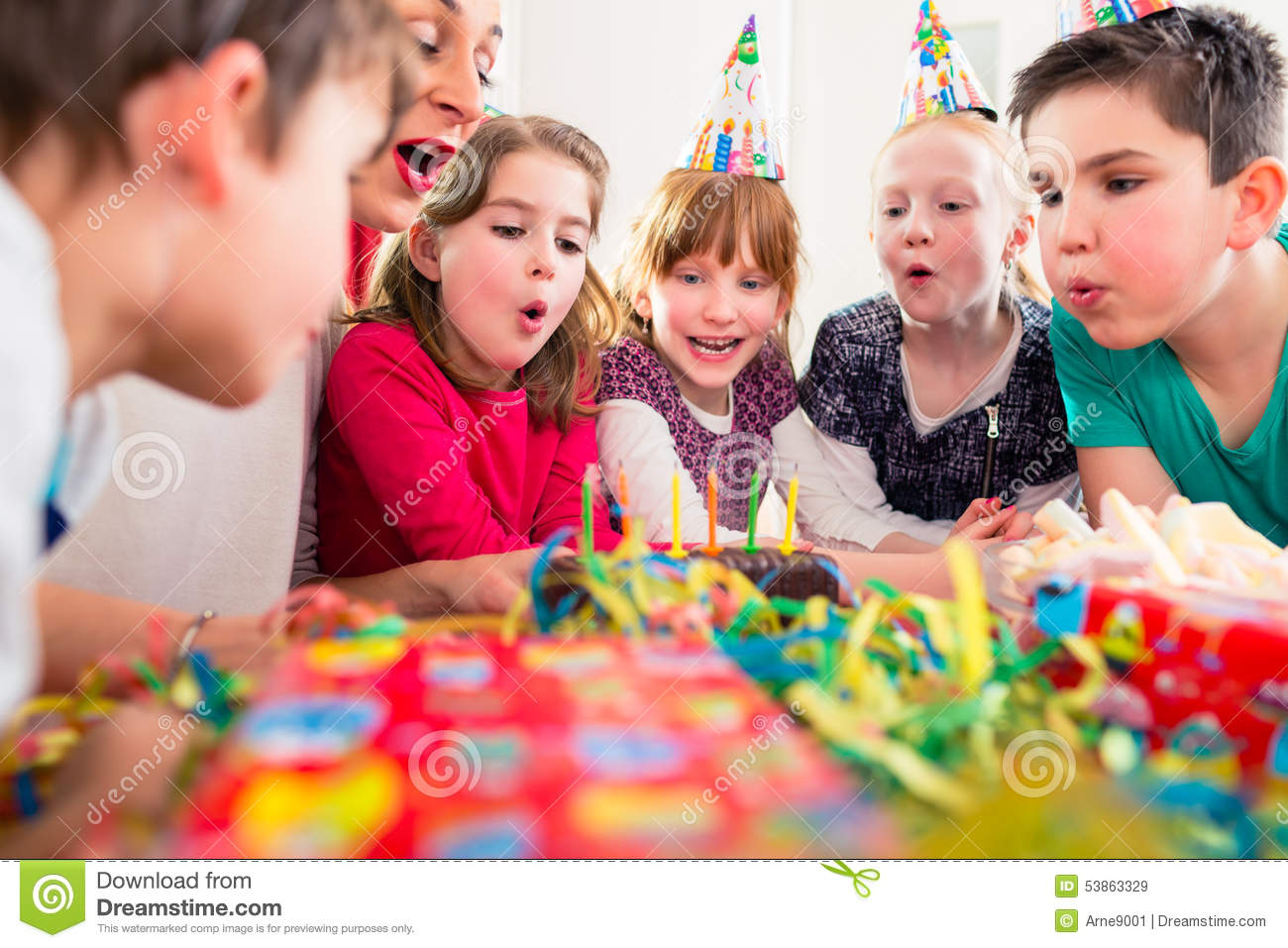child on birthday party blowing candles on cake stock