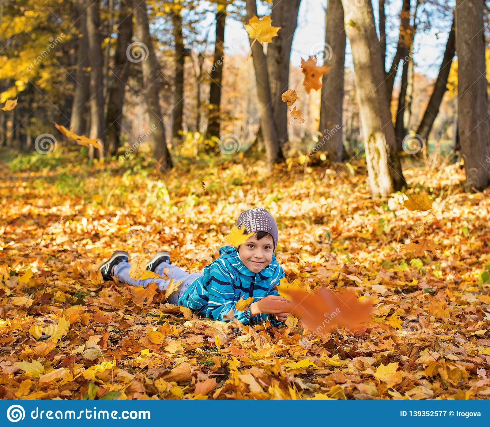 Child boy in autumn park with falling leaves.