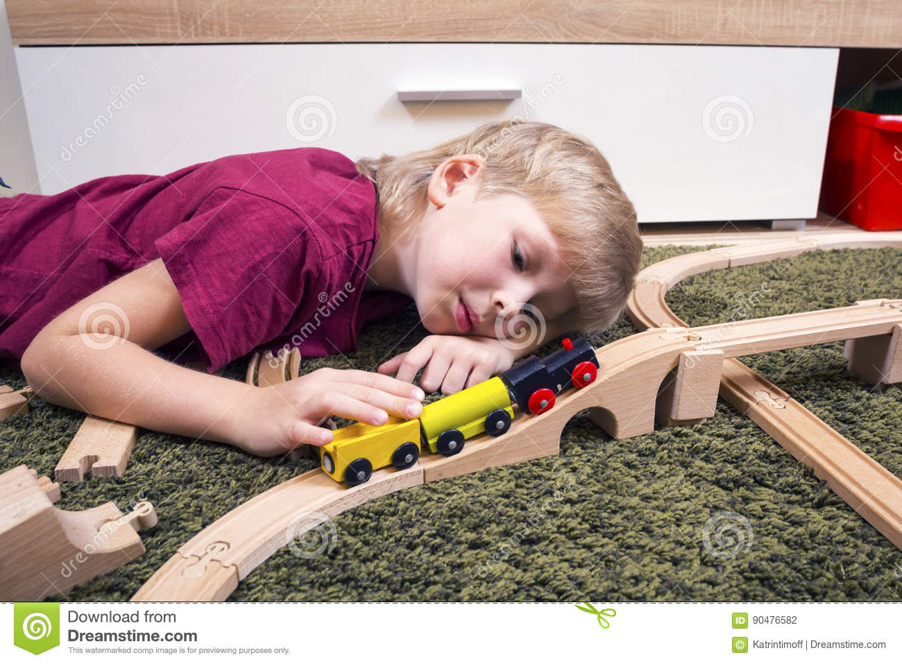 Child boy play with wooden train, build toy railroad at home or