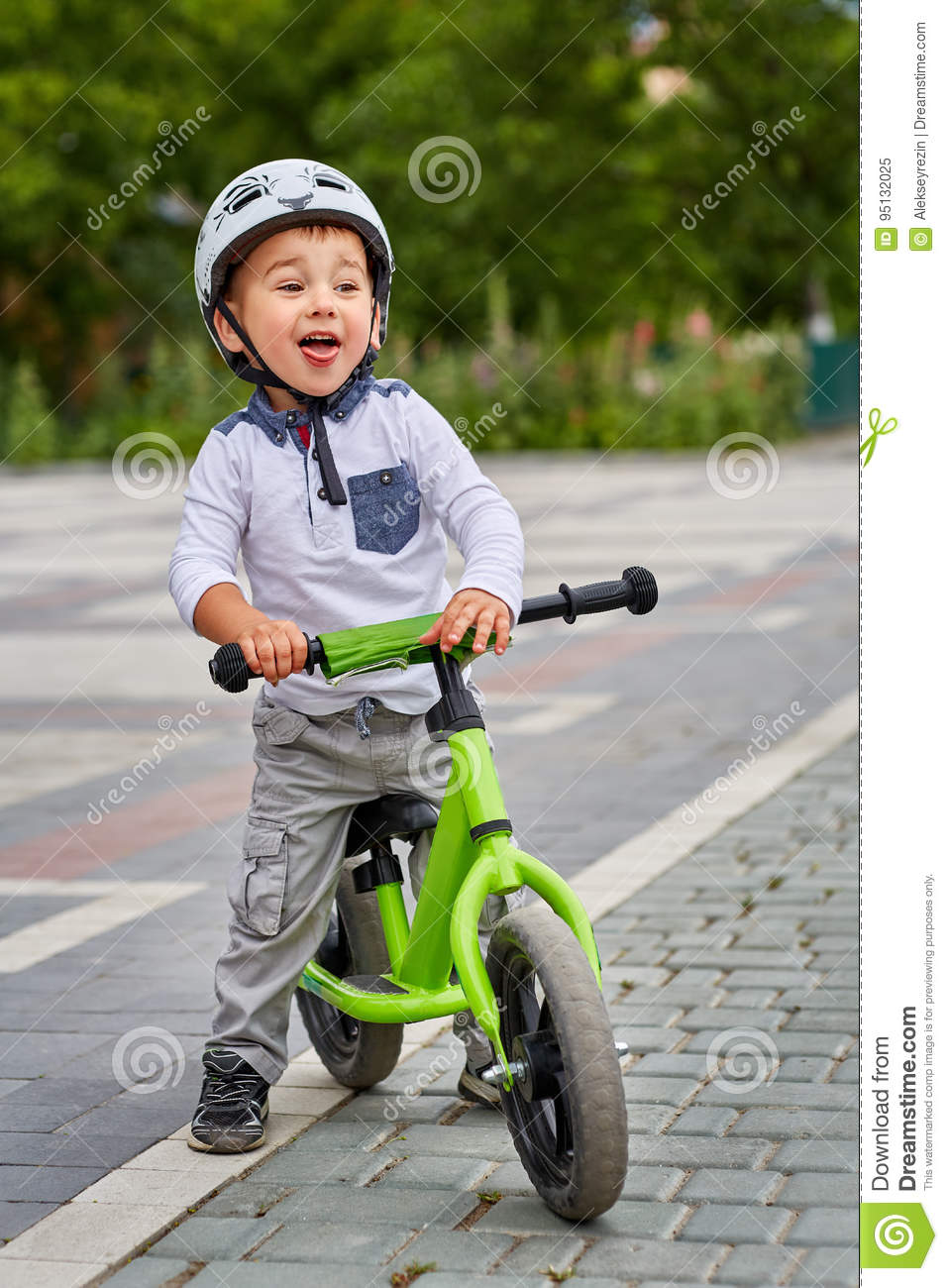 Child Boy In White Helmet Riding On His First Bike With A