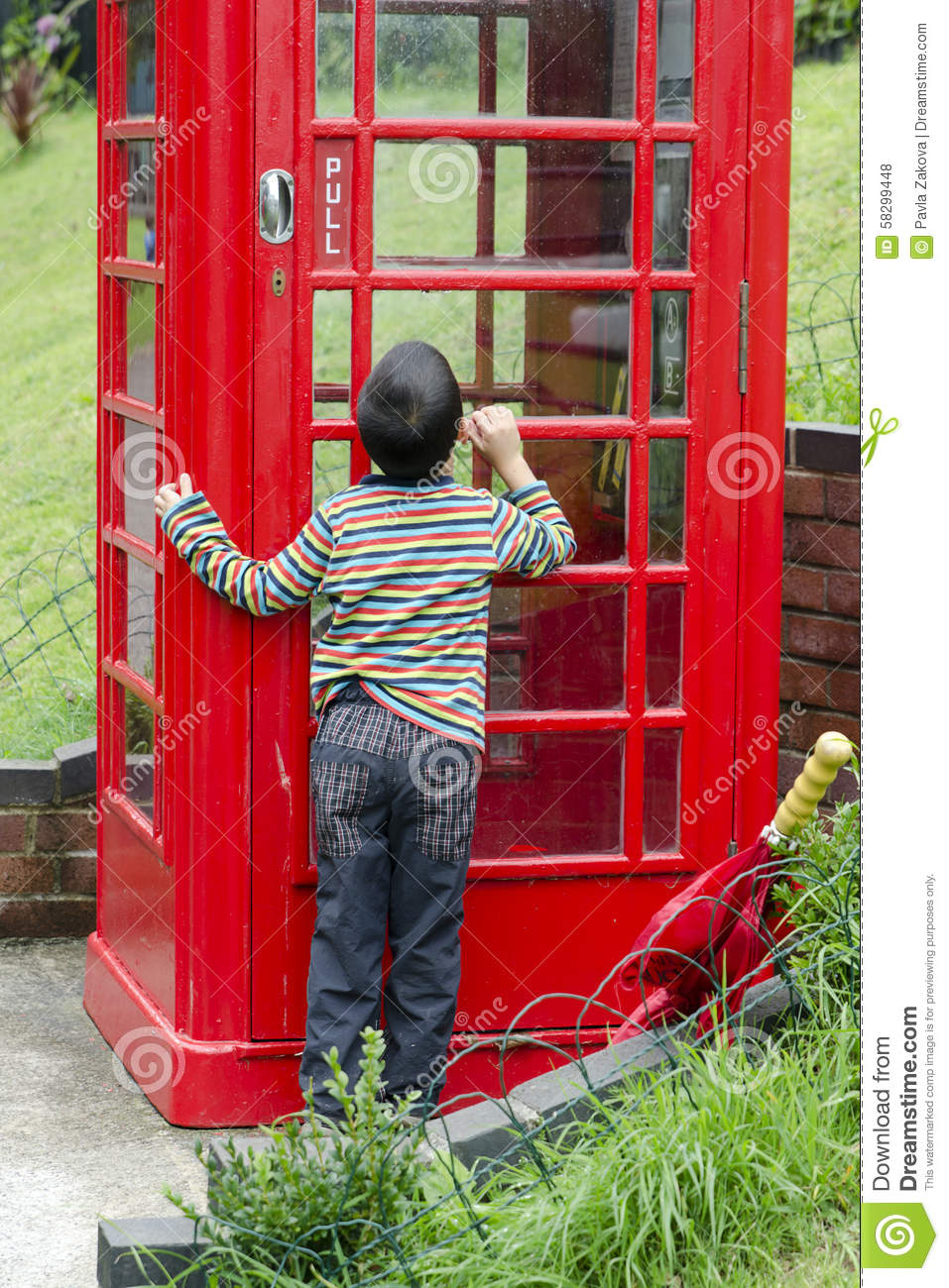 Child by a Brithish phone box