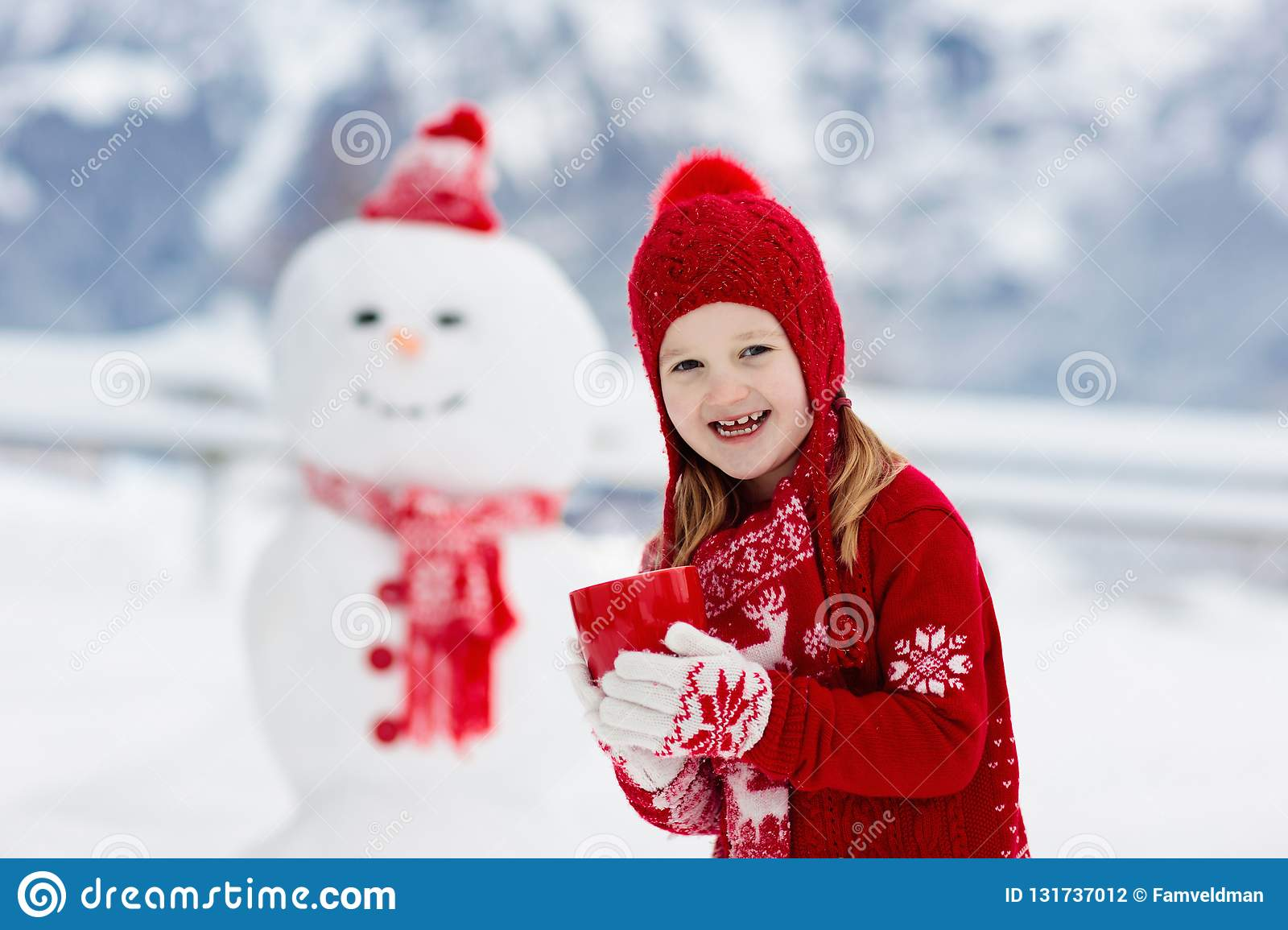 Child building snowman. Kids build snow man. Boy and girl playing outdoors on snowy winter day. Outdoor family fun on Christmas