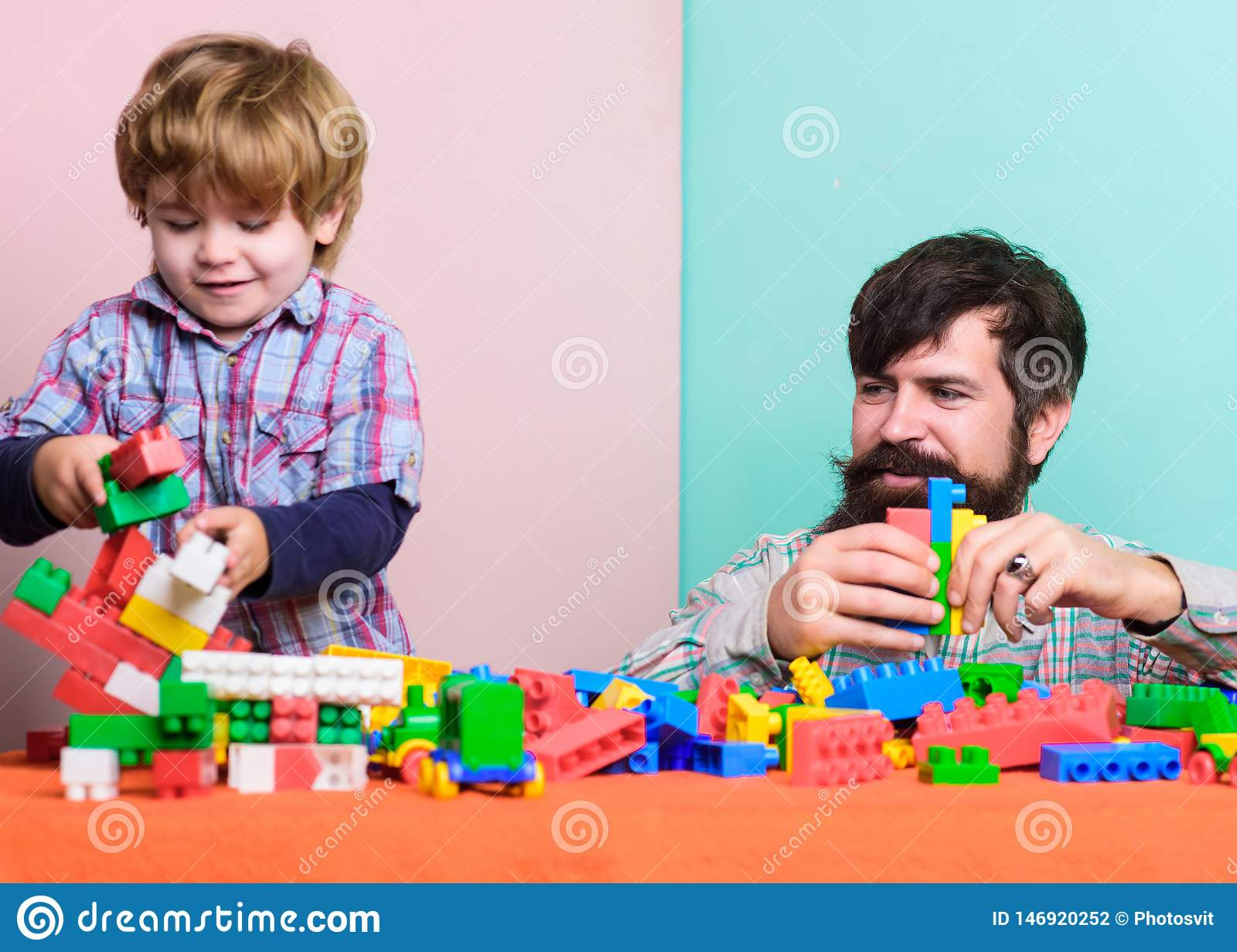 Child care development and upbringing. Father son game. Father and son create colorful constructions with bricks