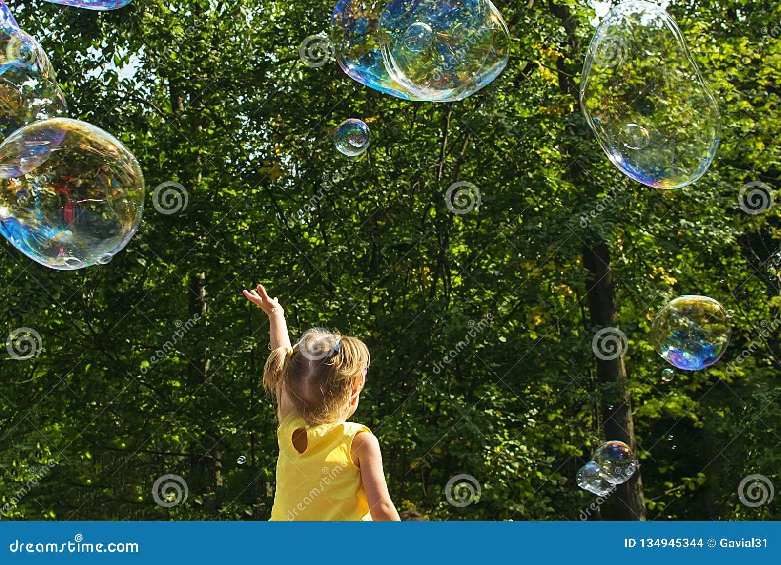 Child catches soap bubbles.