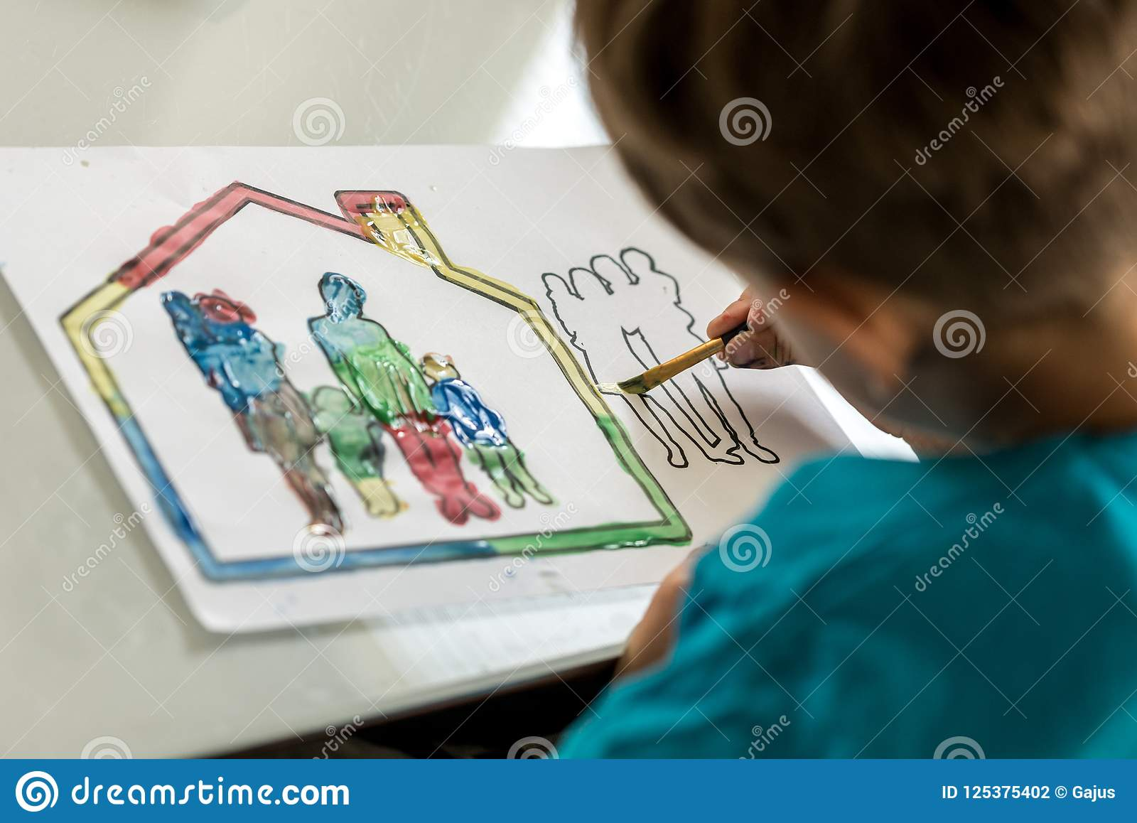 Child Colouring In A Sketch Of A Family Using A Paintbrush Stock ...
