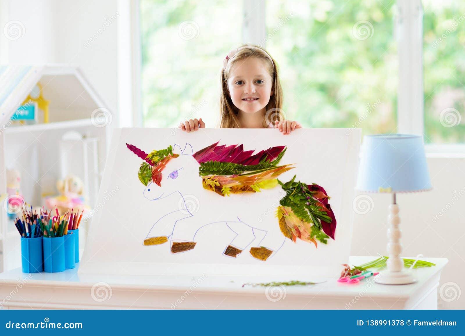 Child drawing unicorn using tree leaves