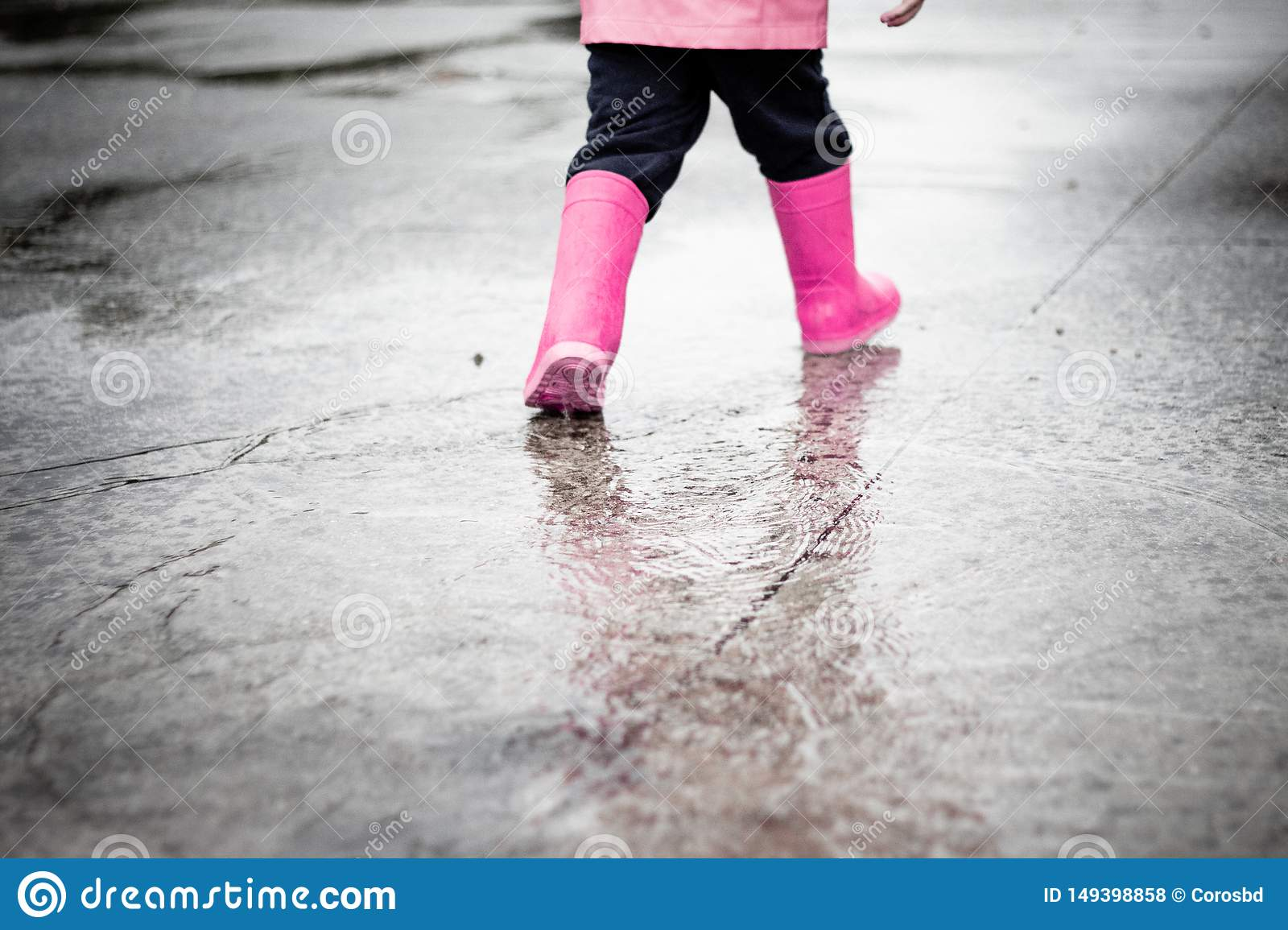 Child dressed in pink clothes jumping in puddles