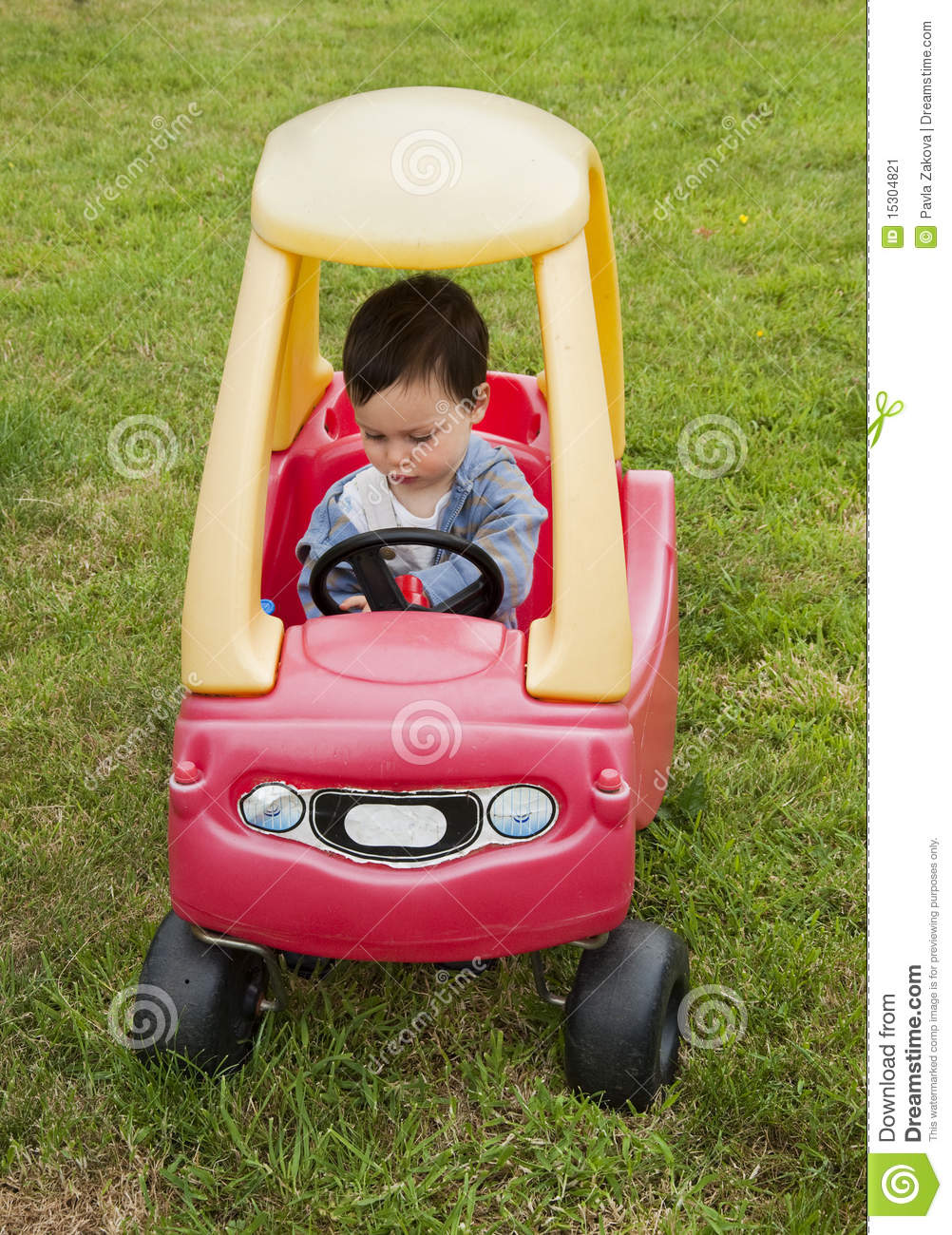 Baby Boy Toy Cars : Baby boy driving a toy car at the playground stock photo
