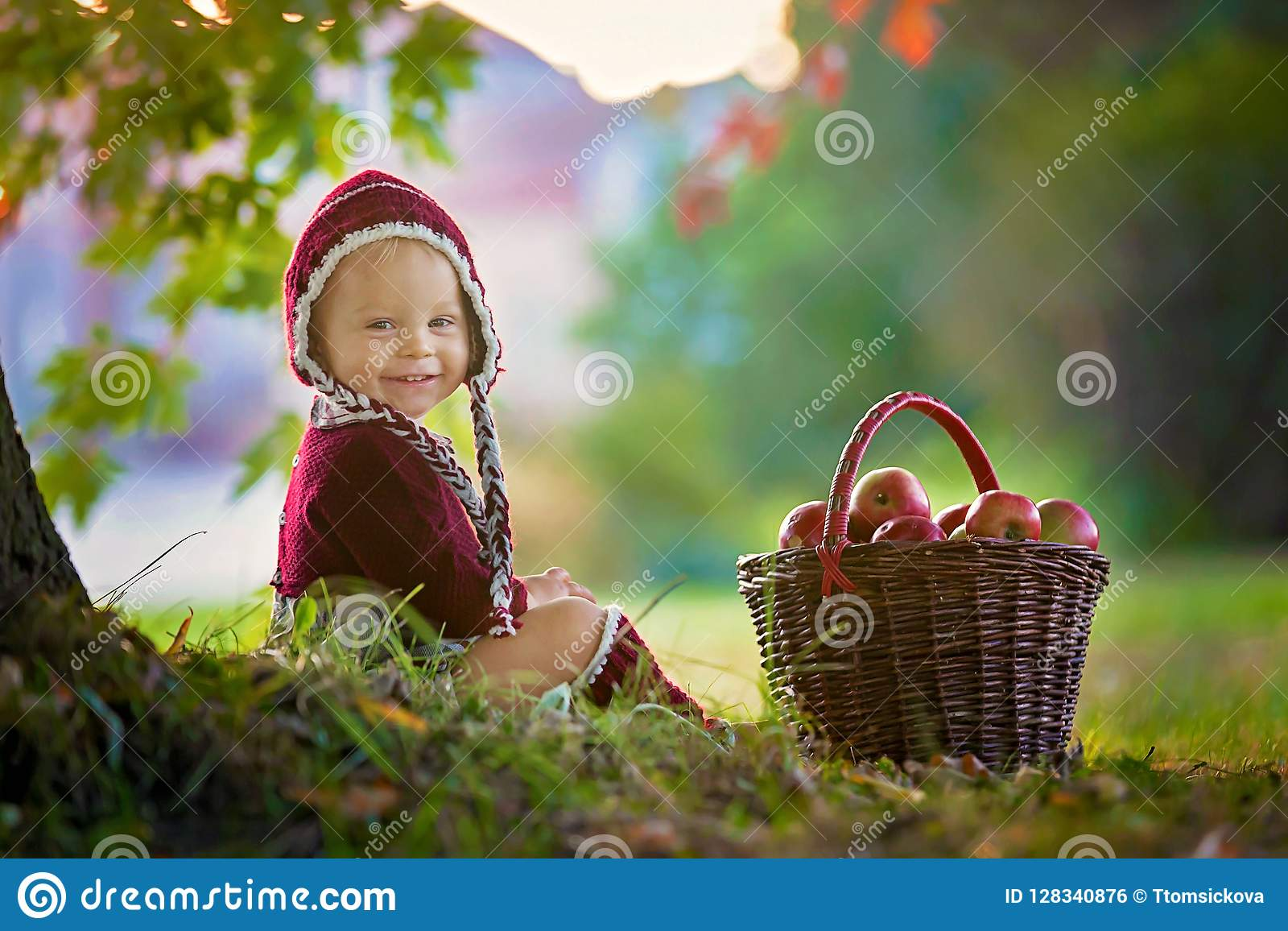 Child with apples in a village in autumn.
