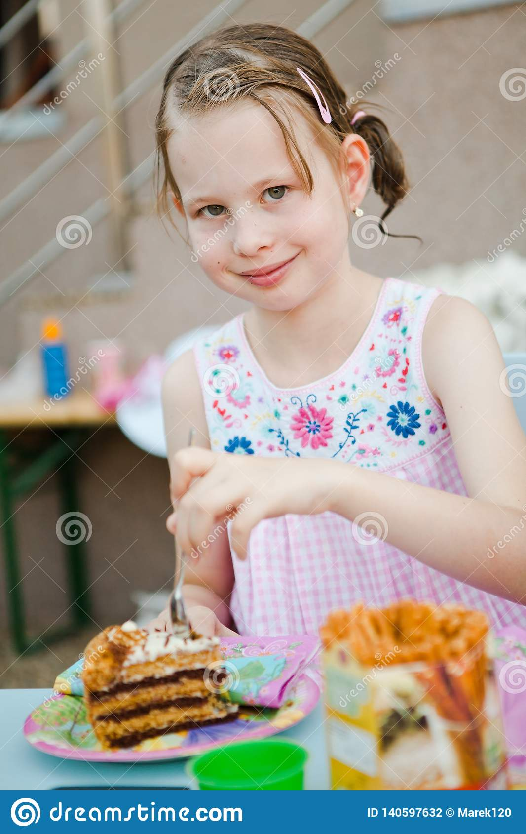 Child eating birthday cake - natural real background
