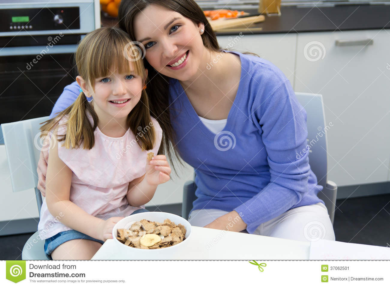 Child Eating Cereals With Her Mom In The Kitchen Stock