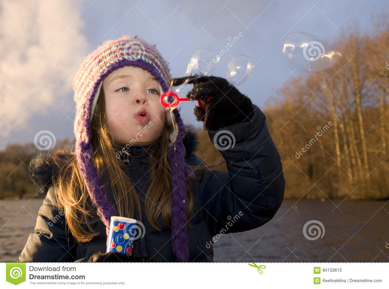 Child enjoys playing with soap bubbles at sunset