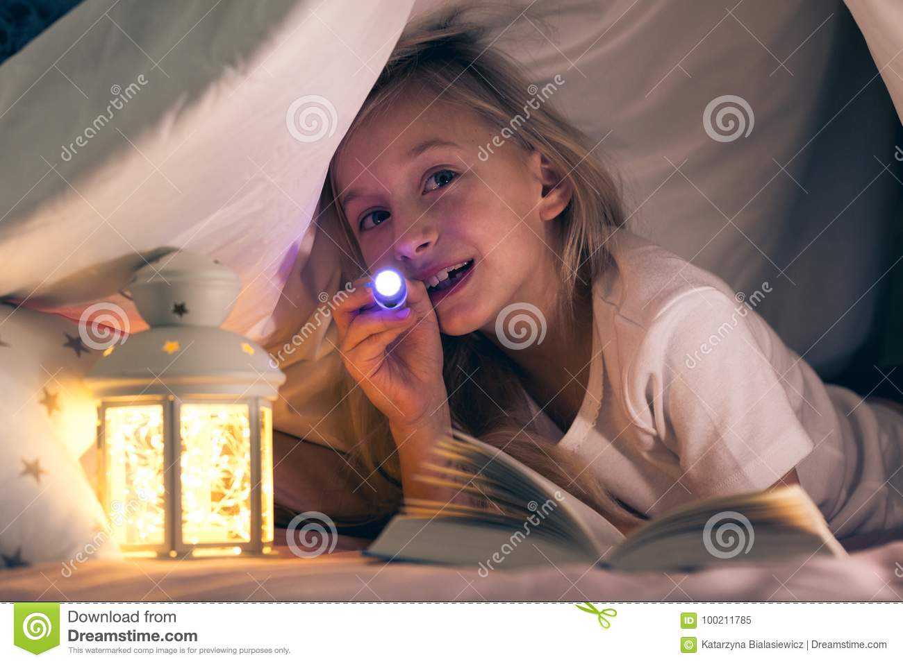Child with flashlight in tent