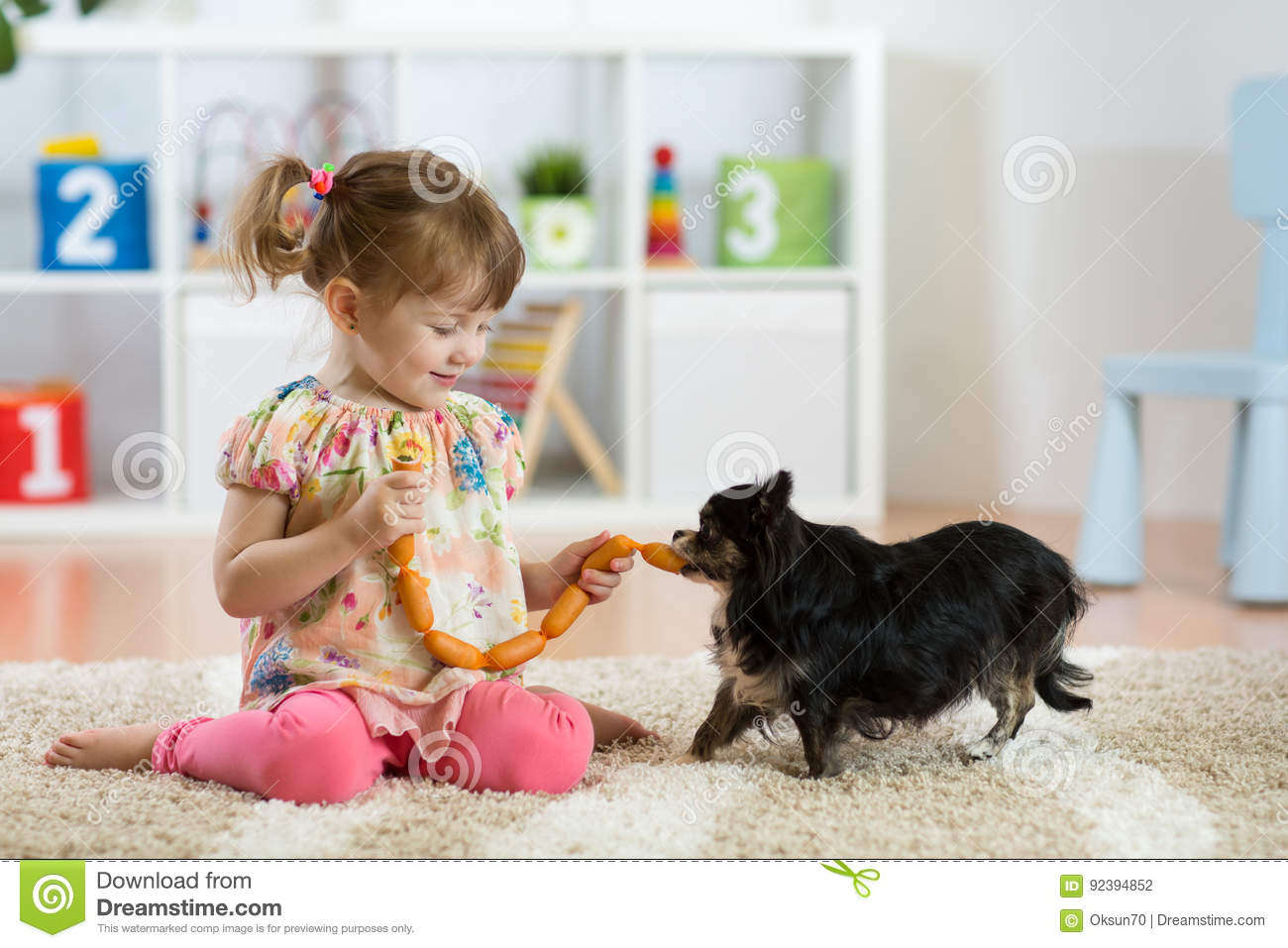 Child girl feeding sausages to her dog on floor in nursery.