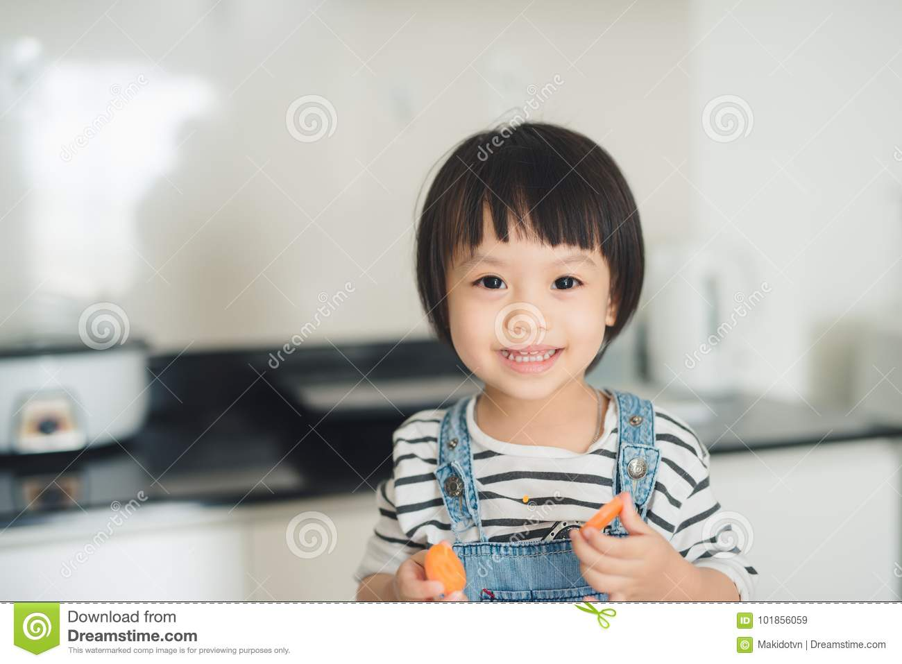 Child girl having fun with carrot. Home kitchen interior with fr