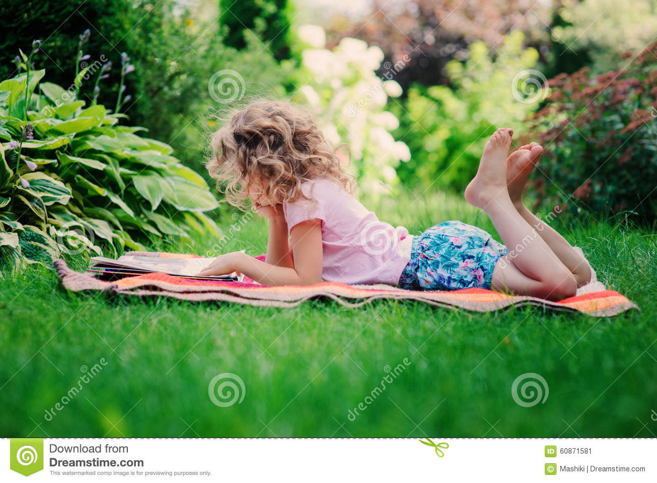 Child Girl Reading Book In The Garden Learning On Summer