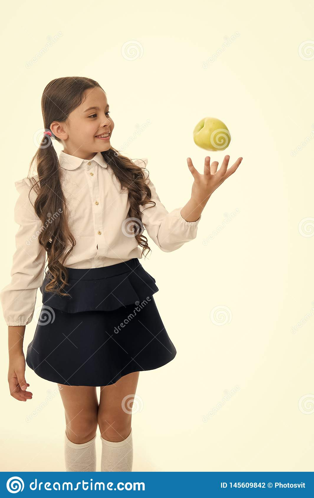 Child girl school uniform clothes toss apple. Girl cute pupil holds apple fruit white background. Child smart kid