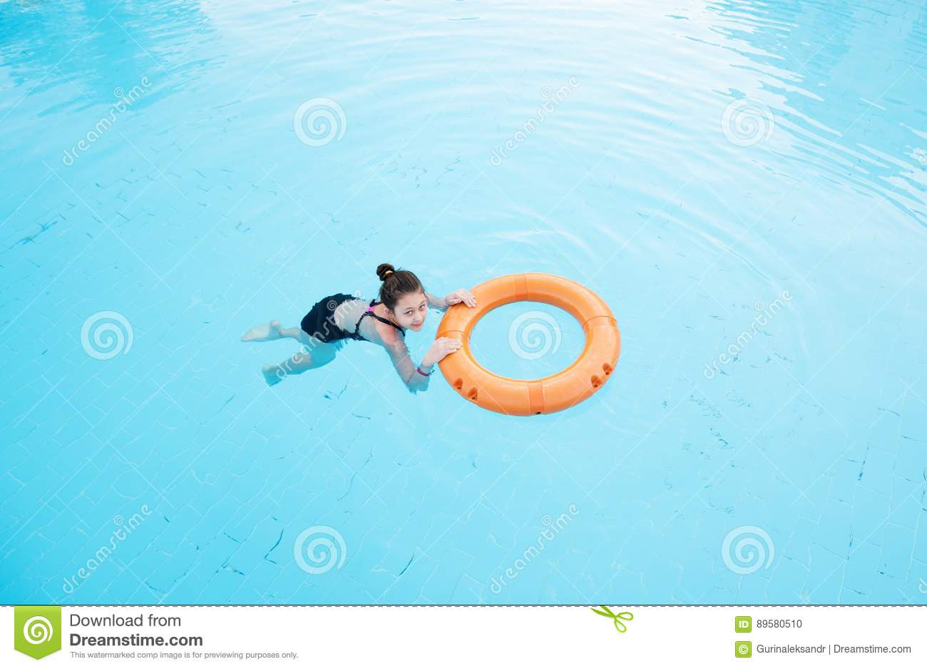 Child girl swims in the pool with lifebuoy