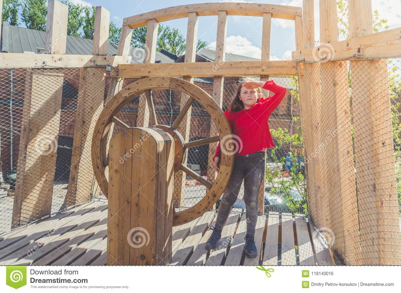Girl On A Wooden Playground In The Form Of A Pirate Ship Stock Photo