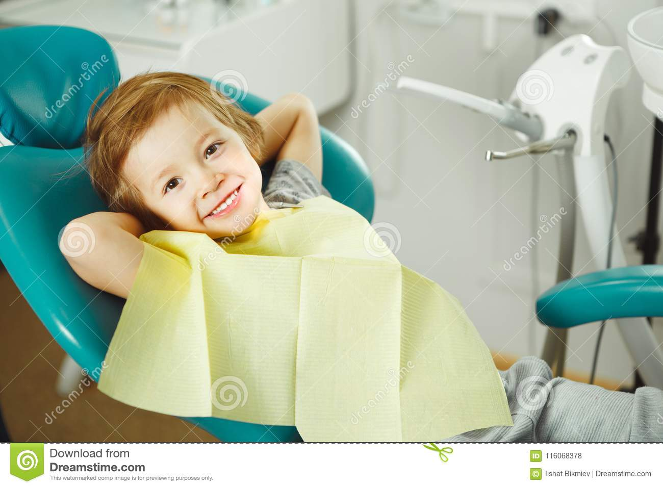 Child in good mood sitting on chair and without fear waiting dentist. Young boy is going to treat teeth. caries