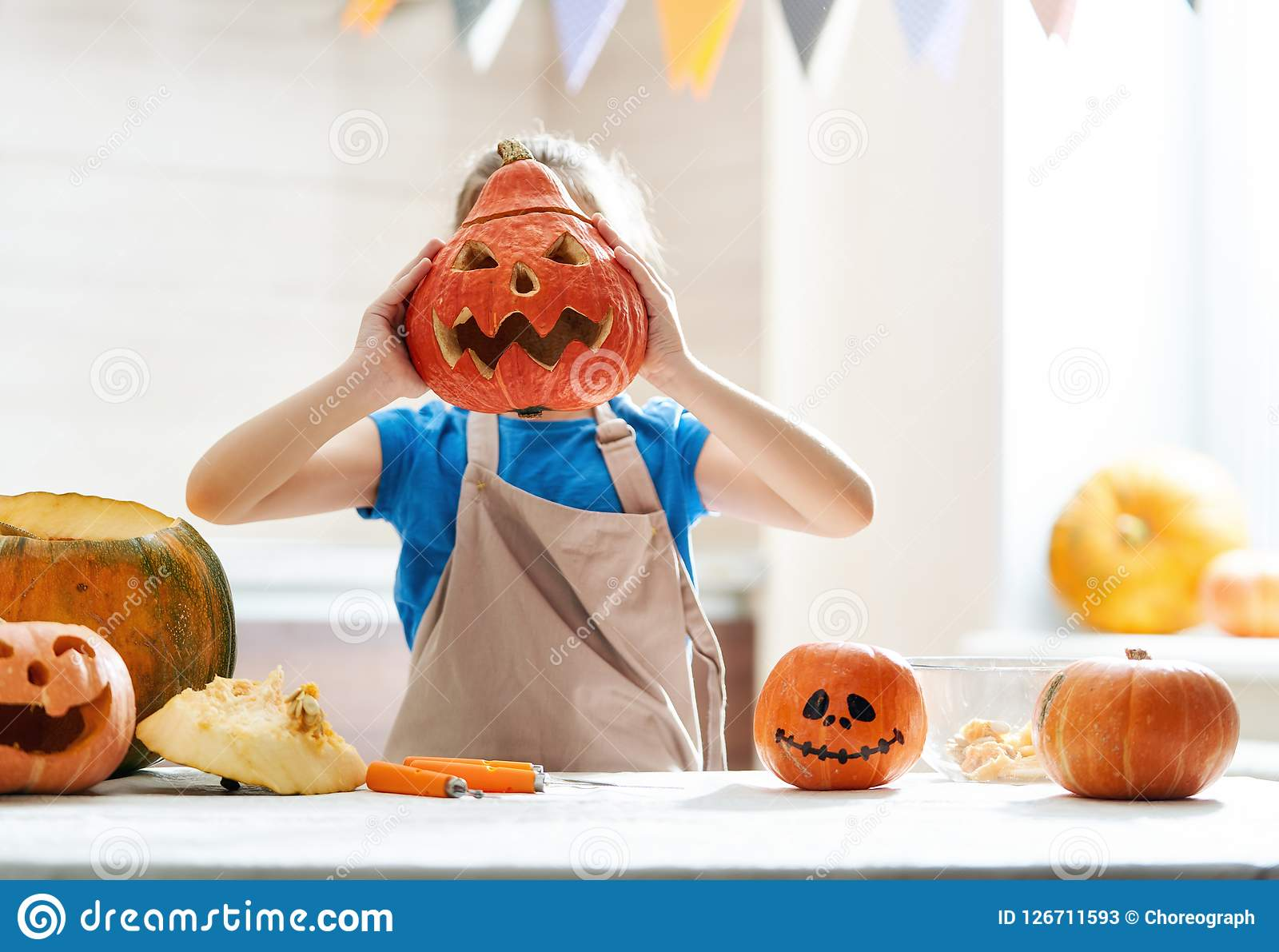Child on Halloween. Happy Halloween! Cute little child girl with carving pumpkin. Family preparing for holiday Stock Photos