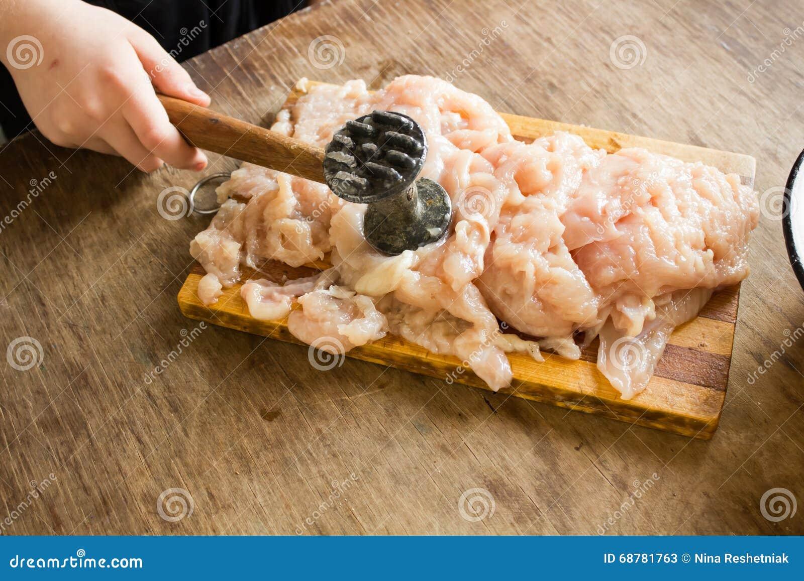 Child hand beat chicken fillet with hammer