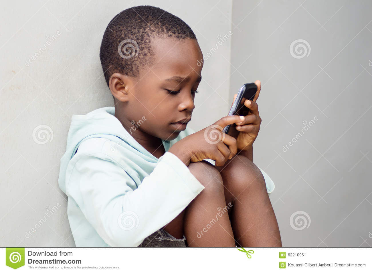 Child handling a mobile phone.