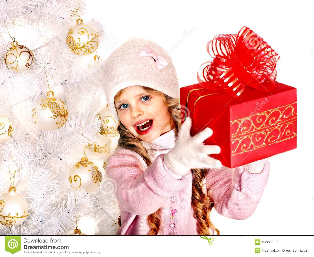 Child in hat and mittens holding red gift box near white Christmas tree.