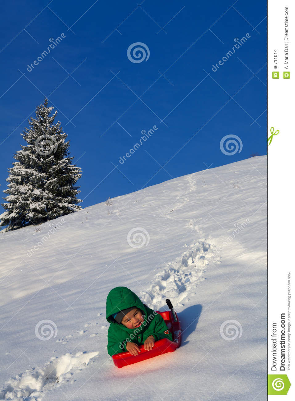 Child having fun in winter, on a sleigh