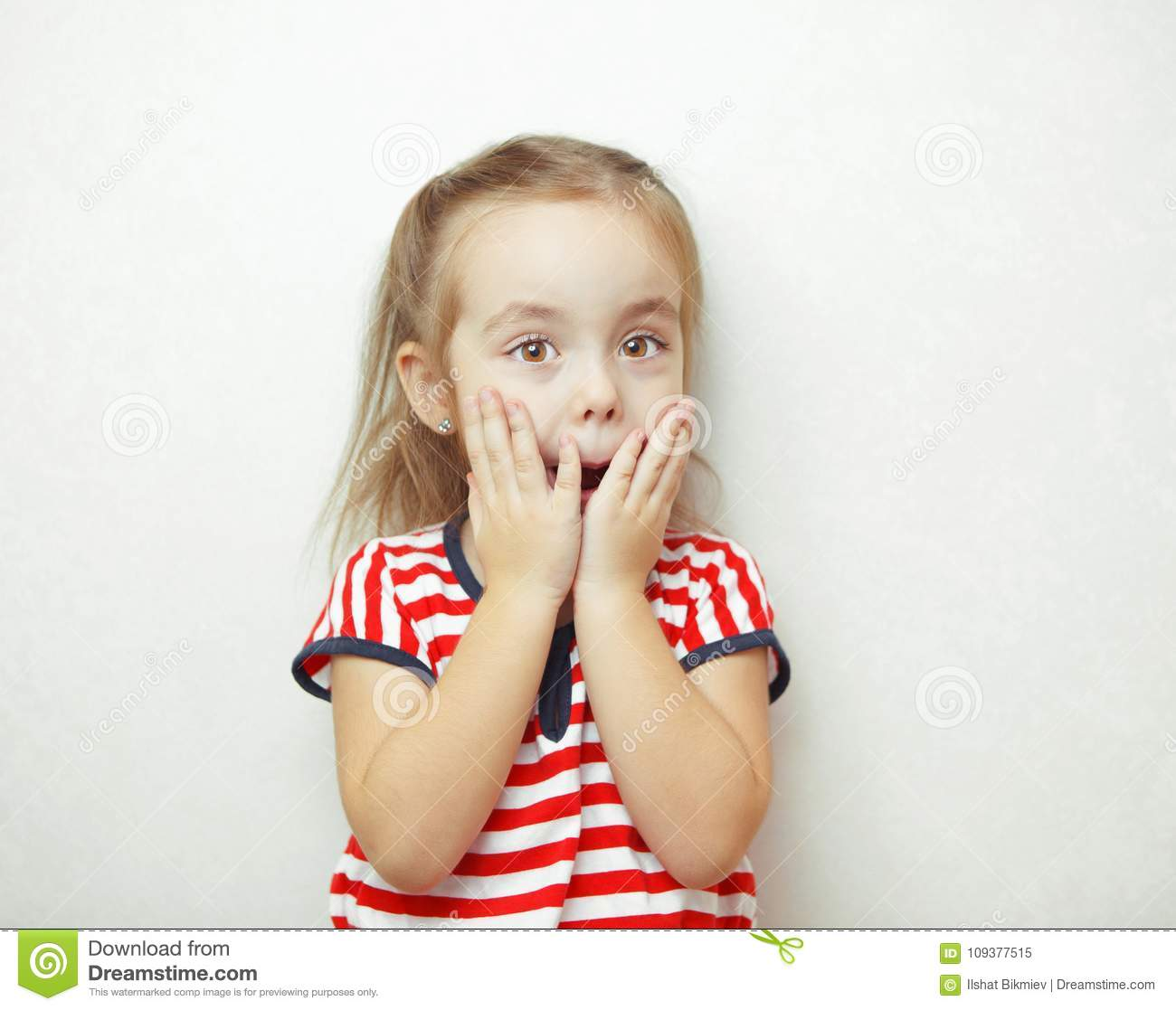 Child with hazel eyes expressing her surprise emotion