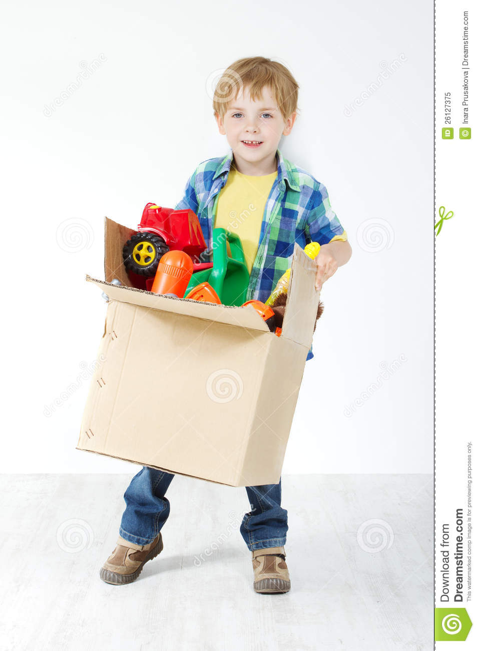 Child Holding Cardboard Box Packed With Toys Stock Image
