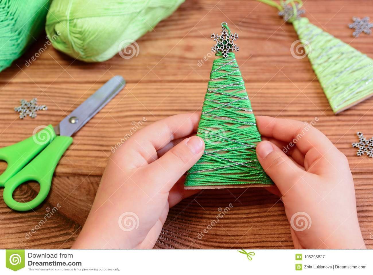 Child Is Holding A Christmas Tree Decoration In His Hands Child Is