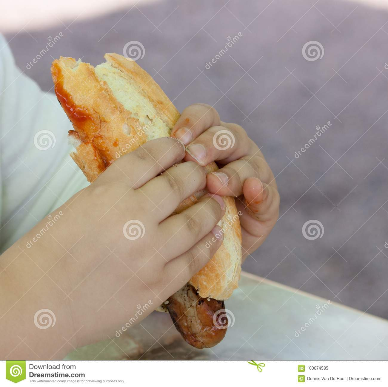 Child eating sausage in bread.