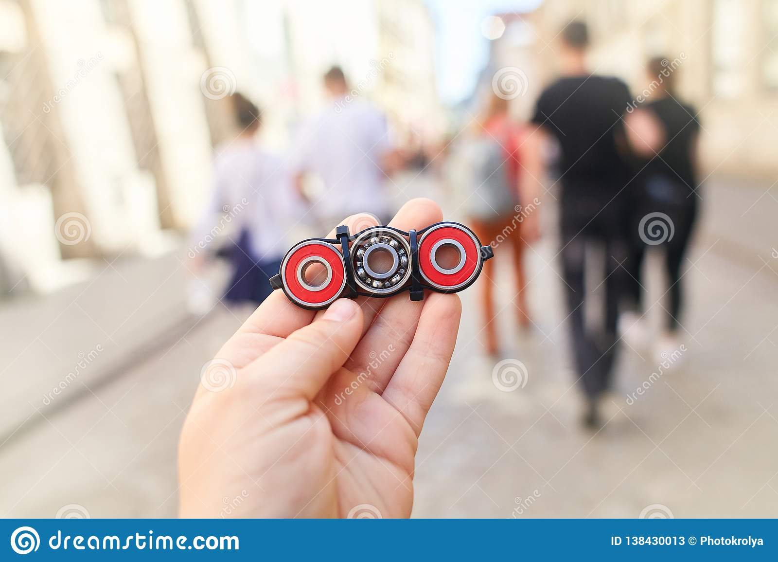 . Child holding unusual metal spinner at blurry people in the street background.