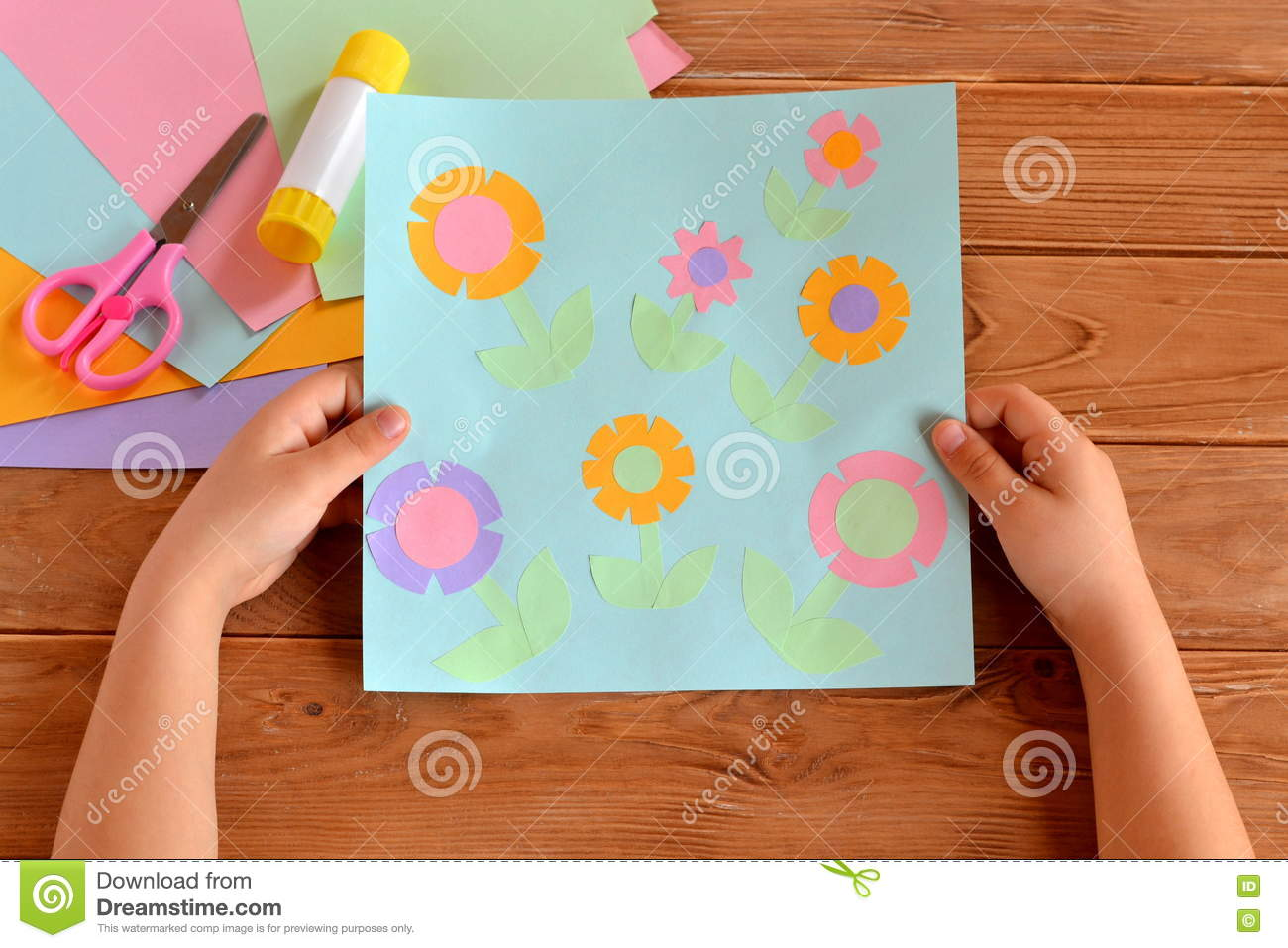 Child Holds A Card With Flowers In His Hands Glue Scissors Paper