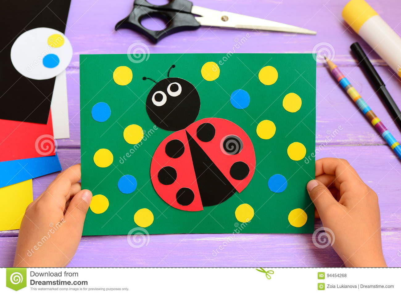 child holds a summer card in his hands child made a paper ladybug