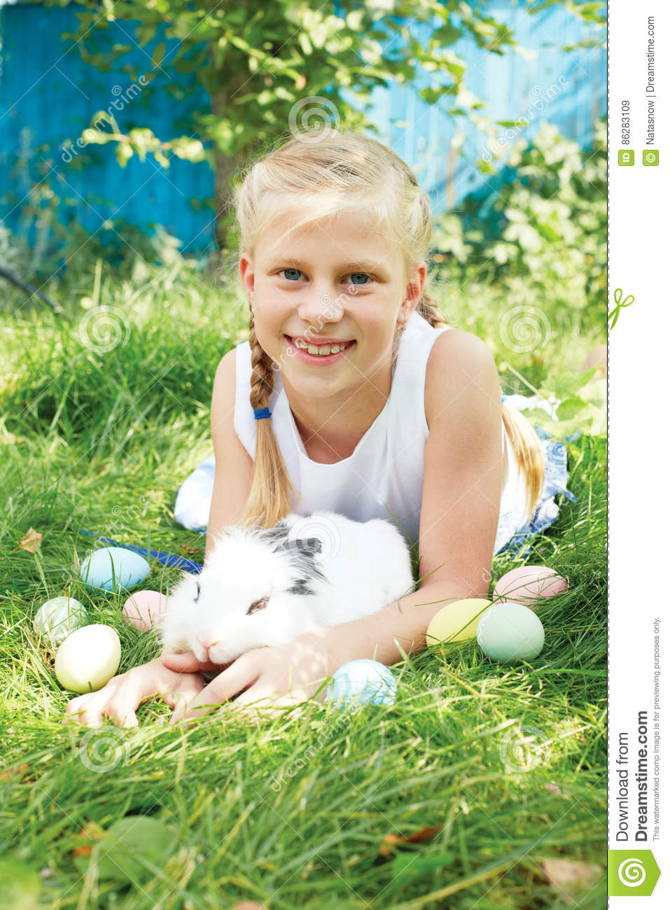 Child hunted on Easter egg in blooming spring garden.