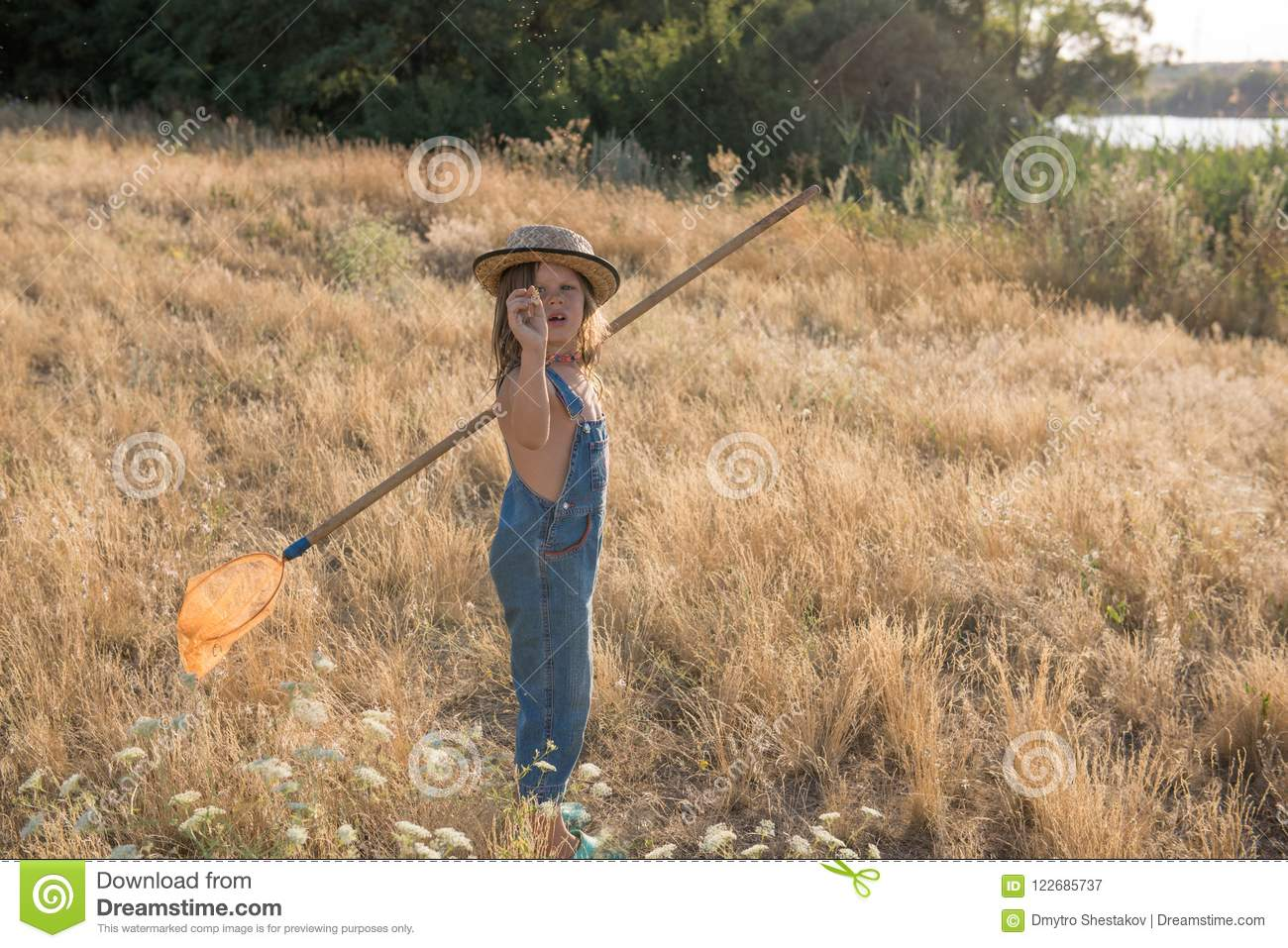 Child with a insect net catches butterfly