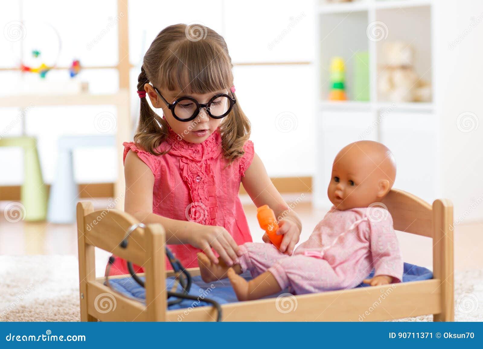 459b176ef7bd3 Child in kindergarten. Kid in nursery school. Little girl playing doctor with  doll