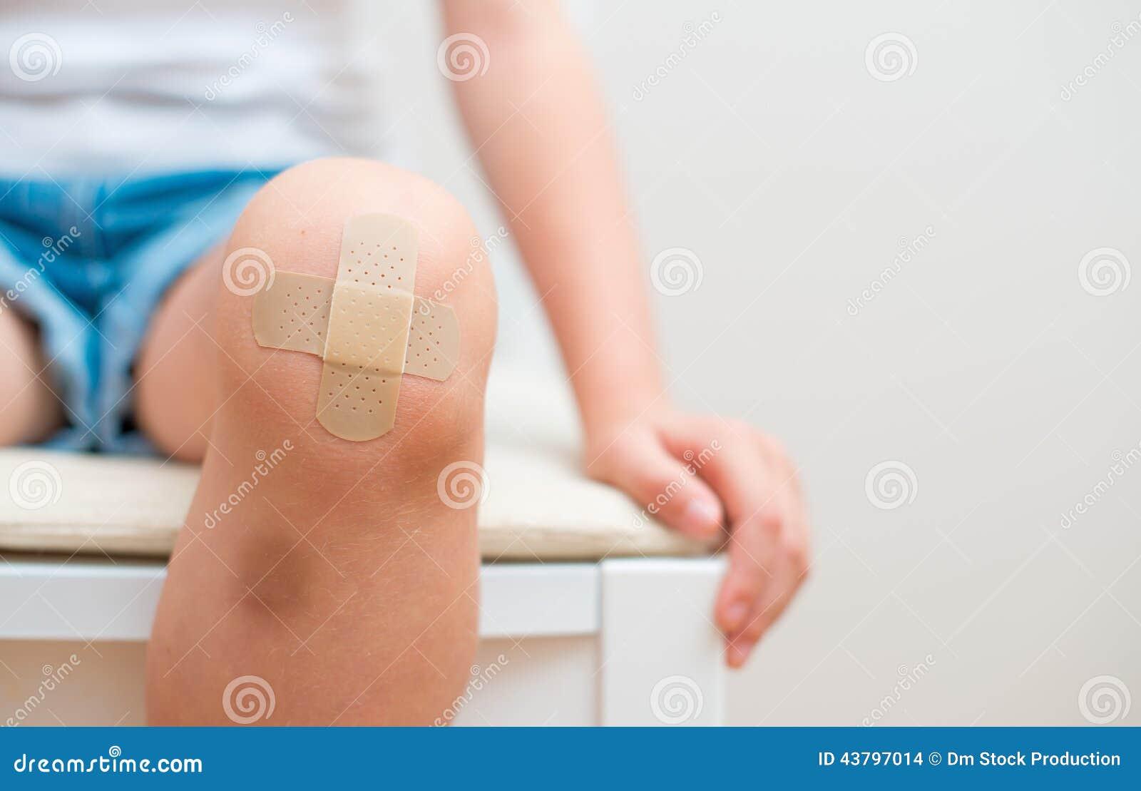 Child knee with adhesive bandage.