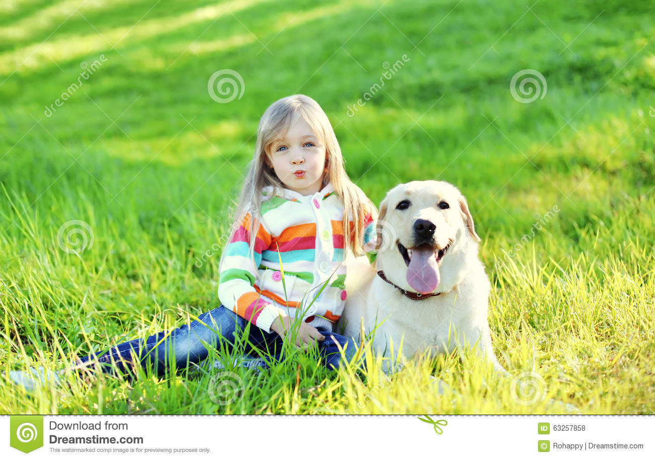 Child and labrador retriever dog sitting on grass in for Dog day sitting