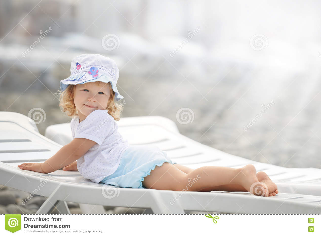 Child laying on the beach chaise long in the sun light
