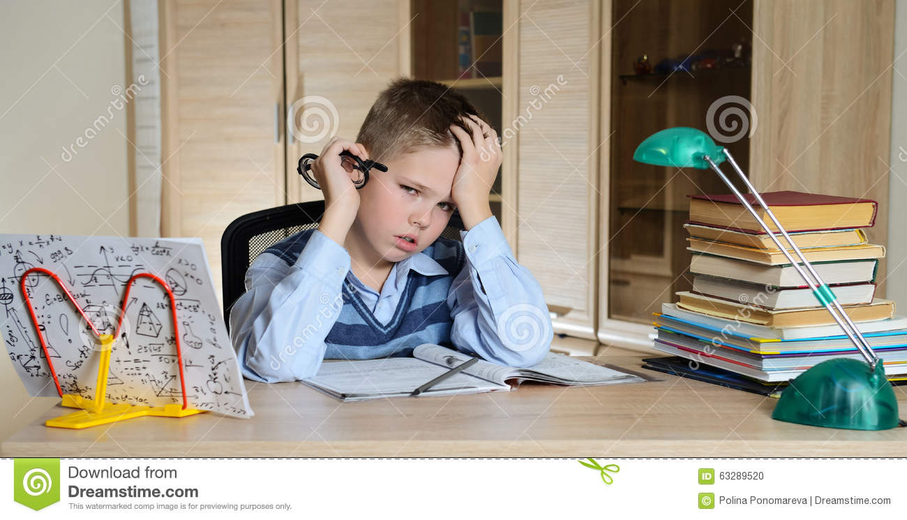 Child with learning difficulties. Tired boy doing homework. Education.