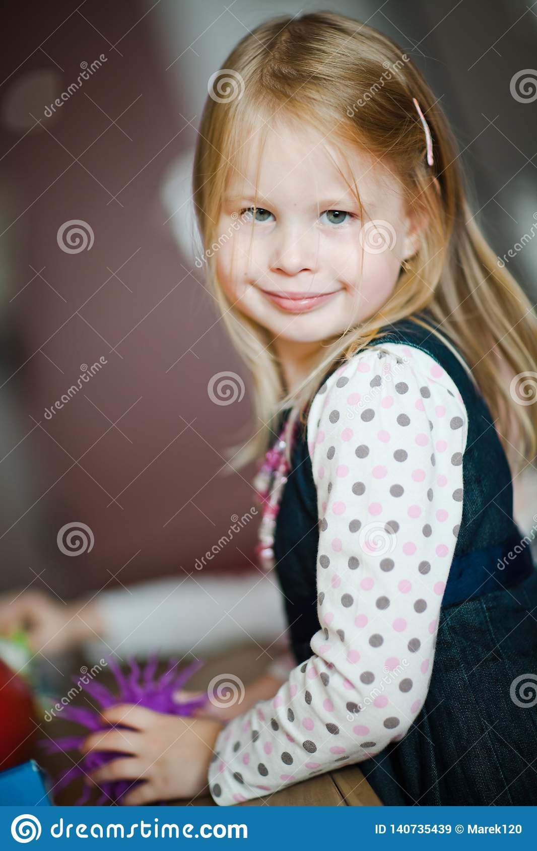 Child with long blond hairs playing - natural posing and smile