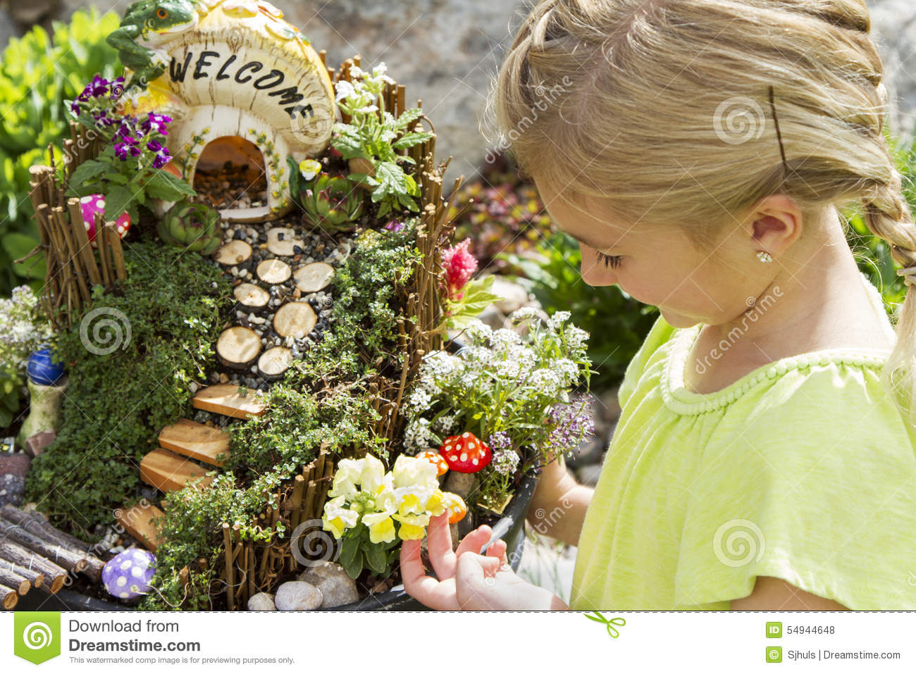 Child Looking At Fairy Garden In A Flower Pot Outdoors Stock Photo