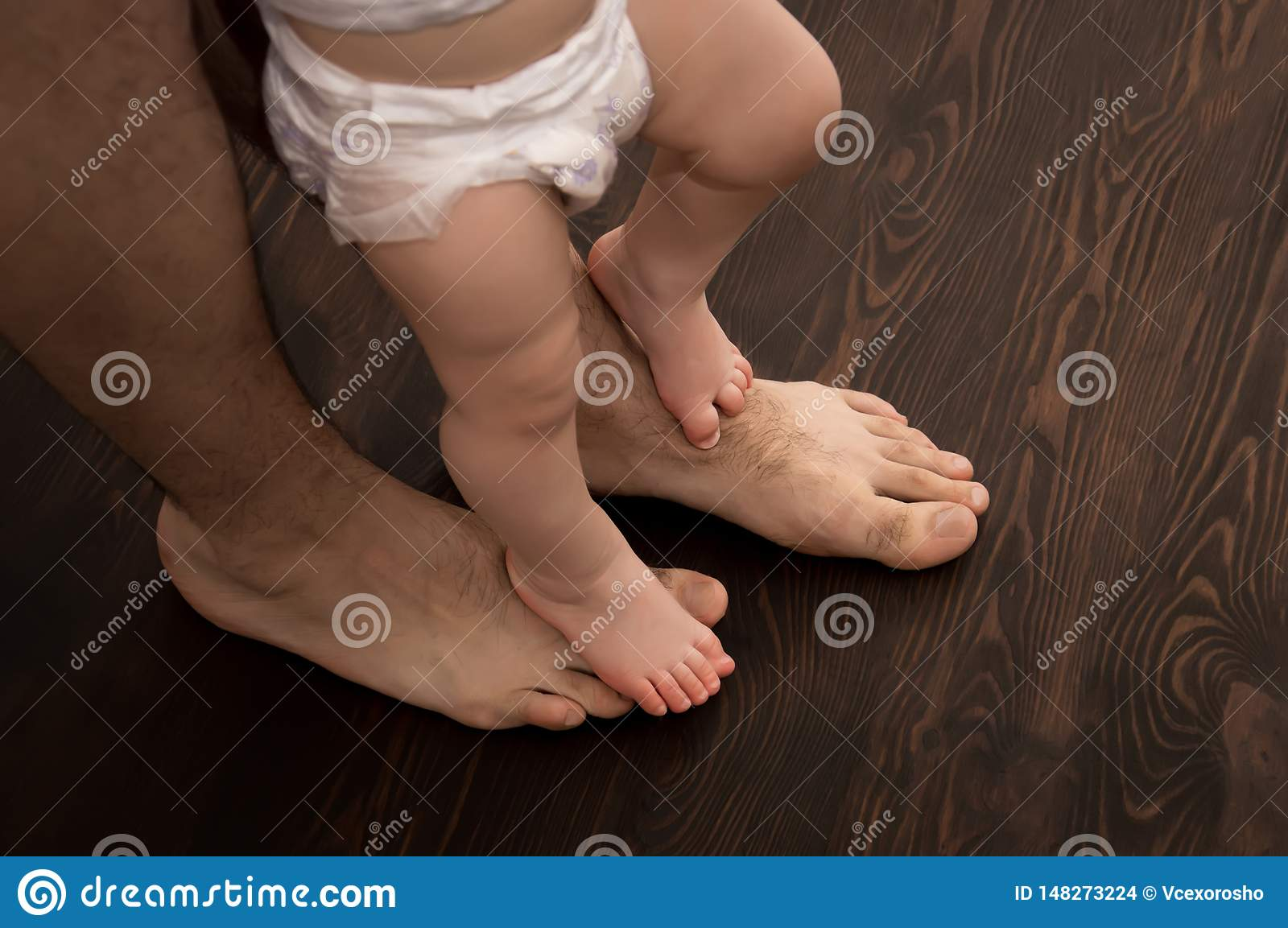 The child makes the first step. Large male legs with small baby legs. Dad helps the child take the first steps