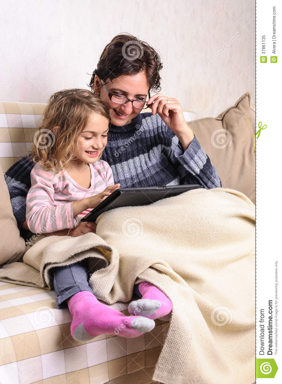 child and mother using tablet on sofa royalty free stock photo image 37861135. Black Bedroom Furniture Sets. Home Design Ideas